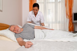 nurse repositioning an elderly man